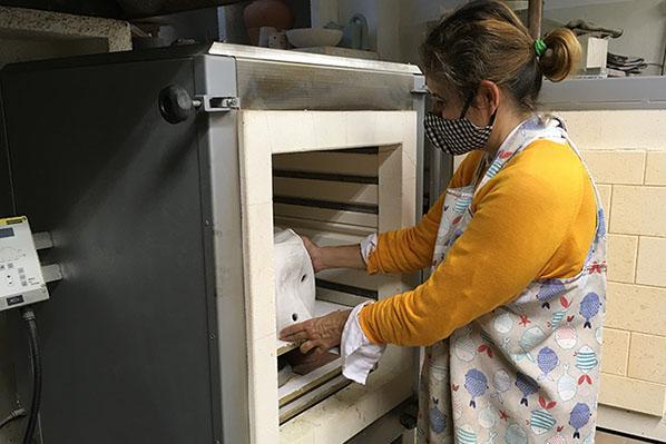 Belén Besga introduciendo pieza de cerámica en el horno
