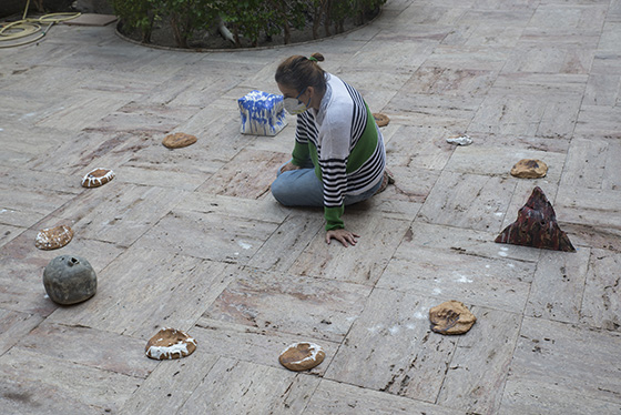 Belén Besga dentro de un círculo de objetos de cerámica